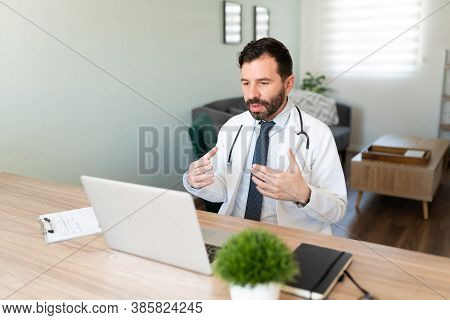 Portrait Of A Virtual Hispanic Doctor Giving Medical Advice To A Patient During A Video Call While W