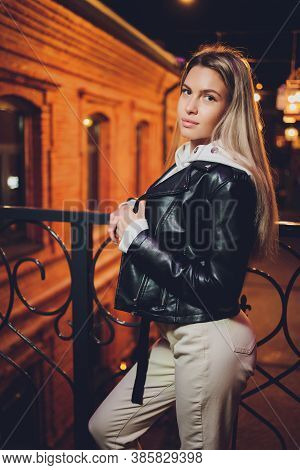 Young Beautiful Pretty Woman Smiling And Posing At City Street In The Night Against Evening Lights B