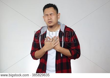 Young Asian Man Wearing Suffer From Chest Pain. Heart Attack Or Asthma Concept