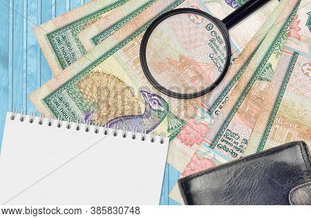 1000 Sri Lankan Rupees Bills And Magnifying Glass With Black Purse And Notepad. Concept Of Counterfe