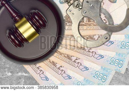 200 Ukrainian Hryvnias Bills And Judge Hammer With Police Handcuffs On Court Desk. Concept Of Judici