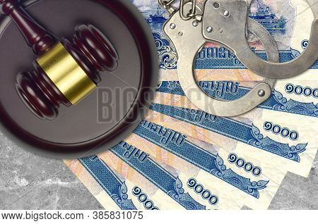 1000 Cambodian Riels Bills And Judge Hammer With Police Handcuffs On Court Desk. Concept Of Judicial