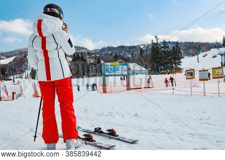 Hokkaido, Japan - December 2019 : Ski Girl With Equipment Ready To Go With Background On Snow In Ski