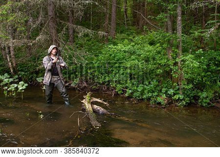 A Fisherman With A Spinning Rod In His Hands Hooked The Fish In The Shallow Water Of A Forest River