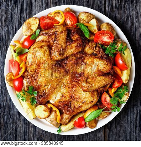 Roast Chicken Served  With Roasted Potato, Fresh Tomatoes, Peppers And Herbs On A White Platter On A
