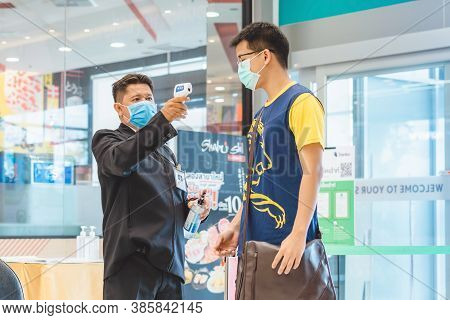 Kanchanaburi, Thailand-july 11,2020:security Guard Use Body Thermometers And Alcohol Gel Injection S