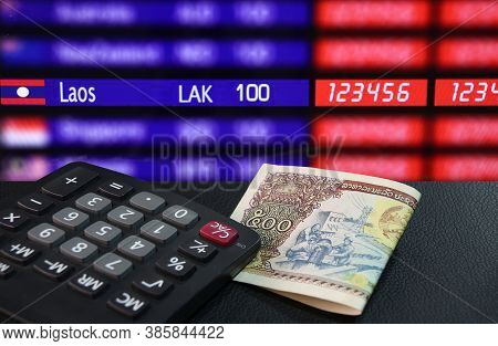 Five Hundreds Of Banknote Currency Lao Kip With Calculator On The Black Floor With Laos Nation Flag