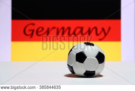 Small Football On The White Floor And German Nation Flag With The Text Of Germany Background. The Co