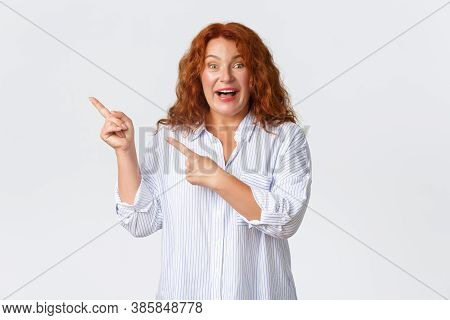 Excited And Impressed Middle-aged Redhead Woman Showing Announcement, Pointing Fingers Upper Left Co
