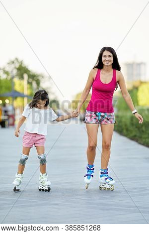 Young Mother And Her Little Daughter Rollerskating In Park