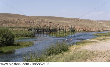 Kurty, Kazakhstan - July 22, 2019: Two People Swimming In The Kurty River Near Kurty Surrounded Buy