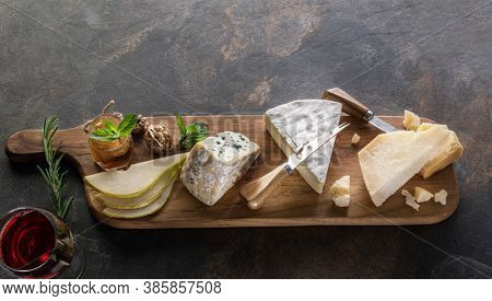 Cheese platter with different cheeses, wine and fruits on stone background. Top view.