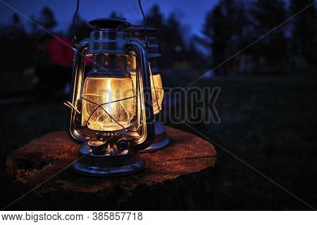 A Old Rustic Oil Lantern On A Wood Block At A Camping Site