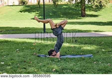 Young Athletic Man In Sportswear Doing Yoga In The Park. Practice Asana Outdoors. People Exercising