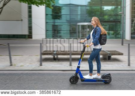 Urban City Lifestyle. Young Beautiful Woman Riding An Electric Scooter In Downtown District. Modern