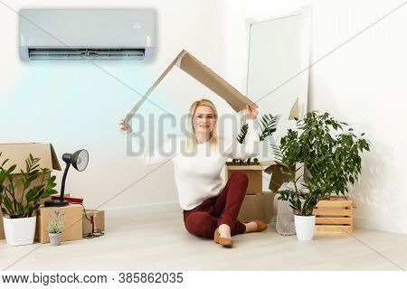 Happy Woman Breathing Fresh Air Sitting. Woman In A New Apartment Under Air Conditioning