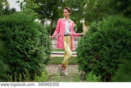 Portrait Of Cute Girl Is Wearing Bright Clothes In The City Park