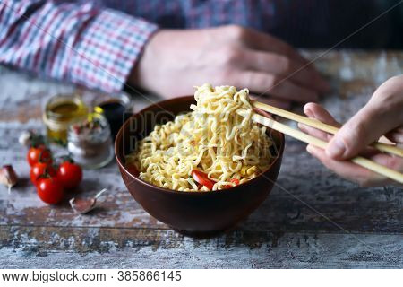 Man Eating Noodles With Chopsticks. A Man Holds Chopsticks With Chinese Noodles.