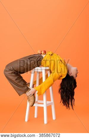 Trendy Woman In Autumn Outfit With Apples On Belly Lying On White Stool And Touching Boots Isolated