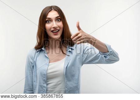 Young Female With Long Chestnut Hair, Dressed In Casual Clothes, Shows Okay Sign With Both Hands, De