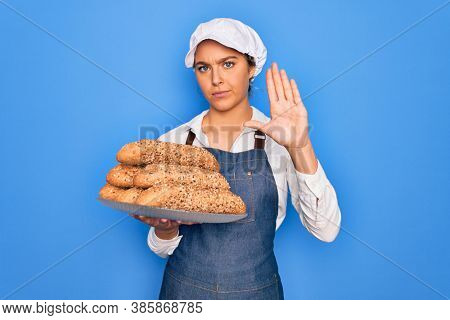 Young beautiful blonde baker woman with blue eyes holding tray with wholemeal bread cereal with open hand doing stop sign with serious and confident expression, defense gesture