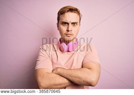 Young handsome redhead man listening to music using headphones over pink background skeptic and nervous, disapproving expression on face with crossed arms. Negative person.