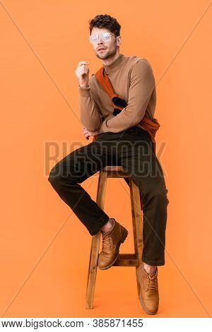 Pensive Man In Autumn Outfit And Glasses Sitting On Wooden Stool On Orange