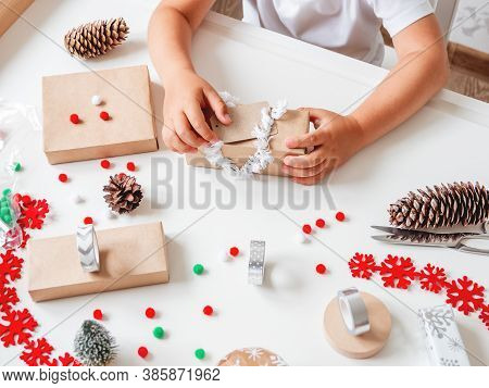 Kid Wraps Handmade Christmas Presents In Craft Paper With Colorful Pompons And Snowflake Ribbons. Ch