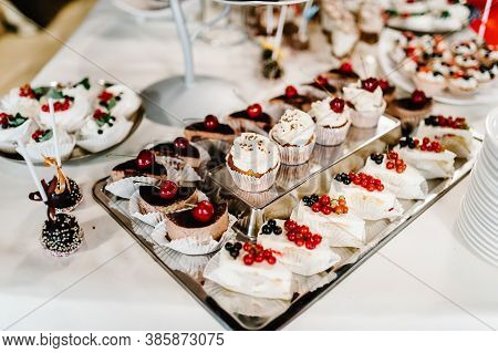 Sweet Table. A Plate Of Cakes And Muffins With Cream With Berries. Table With Sweets, Candy, Buffet.