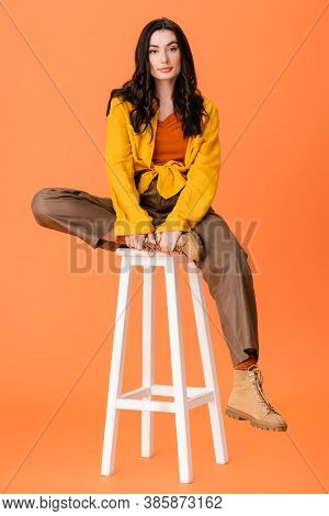 Full Length Of Fashionable Woman In Autumn Outfit Sitting On White Stool And Looking At Camera On Or