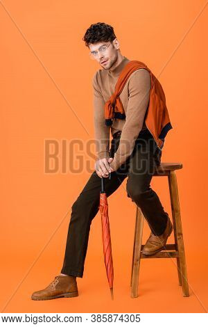 Man In Autumn Outfit And Glasses Holding Umbrella While Sitting On Wooden Stool On Orange