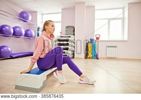 Sports and health concept. Beautiful athletic girl is working out in the gym. Step aerobics, fitness.