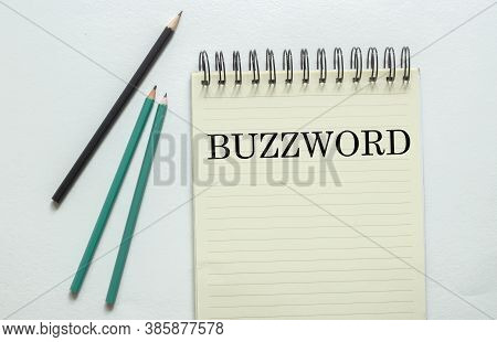 Two Green One Black Pencil With Text Buzzword In The Notebook On The White Background