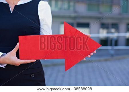 Business woman holding red arrow pointing to the right