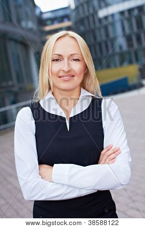 Portrait of happy attractive business woman standing outside the office