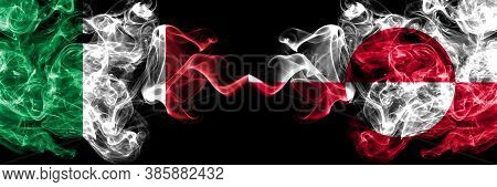 Italy Vs Greenland Smoky Mystic Flags Placed Side By Side. Thick Colored Silky Abstract Smoke Flags