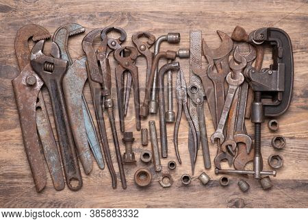 Collection of vintage metal tools such as wrenches, spanners and other on old wooden background, top view