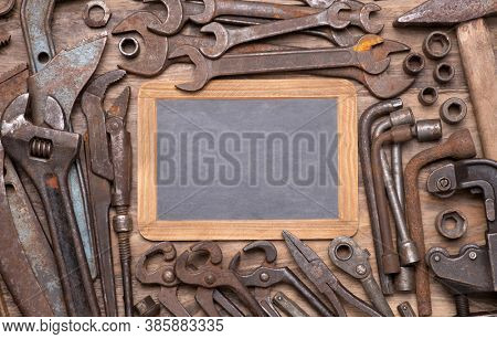 Collection of vintage tools such as wrenches, spanners and other on old wooden background, top view