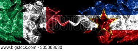 Italy Vs Yugoslavia Smoky Mystic Flags Placed Side By Side. Thick Colored Silky Abstract Smoke Flags