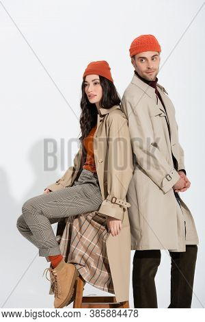 Stylish Woman In Trench Coat Sitting On Stool And Looking Away Near Trendy Man On White