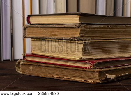 Vvintage, Antiquarian Books Pile On Wooden Surface Against The Background Of New Books Standing In A