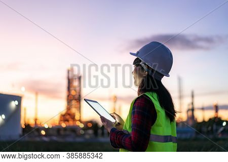 Asian Woman Petrochemical Engineer Working At Night With Digital Tablet Inside Oil And Gas Refinery