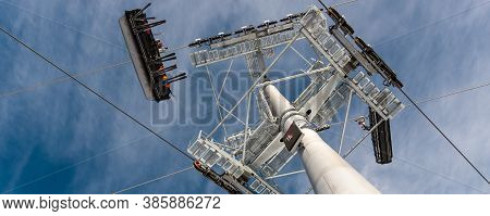 Bottom Up Overhead View Of Big Metal Pillar With Ski Lift Ropeway Crossroad Intersection On Hilghlan