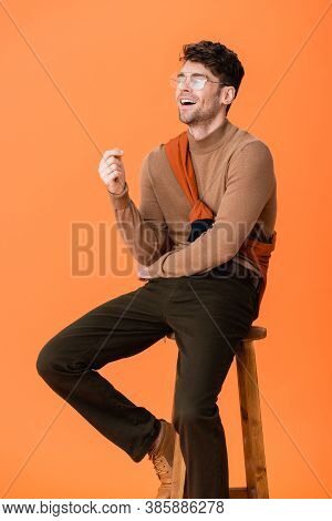Excited Man In Autumn Outfit And Glasses Sitting On Wooden Stool And Laughing On Orange