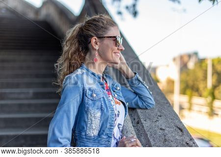 Young Caucasian Urban Woman Elbowing On Stone Railing In Park, Budapest, Hungary