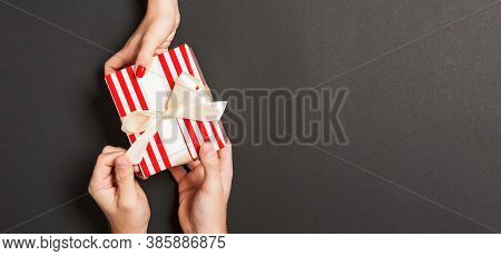 Top View Of A Woman And A Man Giving And Receiving A Present On Colorful Background. Love And Relati