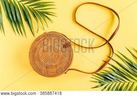 Fashionable Handmade Natural Round Rattan Bag And Tropical Leaves On Yellow Background.
