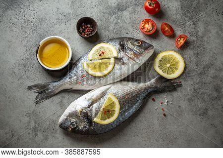 Raw Fish Dorado With Lemon, Cut Cherry Tomatoes, Olive Oil, Seasonings On Gray Concrete Background R