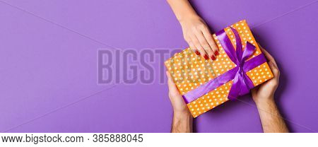 Top View Of Couple Giving And Receiving A Gift On Colorful Background. Romantic Concept With Copy Sp