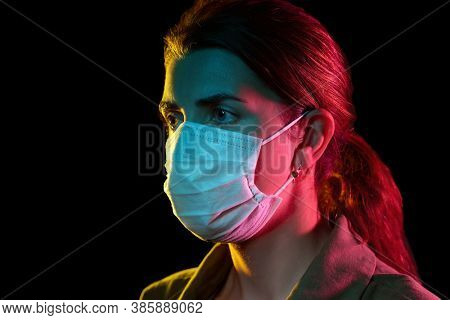 health, safety and pandemic concept - young woman wearing protective medical mask over black background